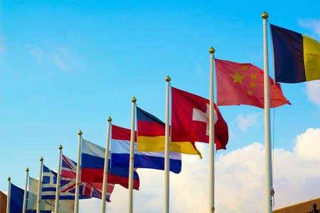Flags of different countries flapping in wind against blue sky