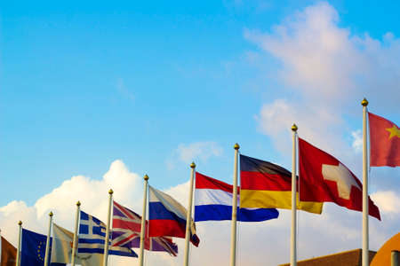 tenure: Flags of different countries flapping in wind against blue sky