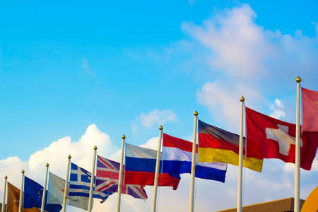 different countries: Flags of different countries flapping in wind against blue sky