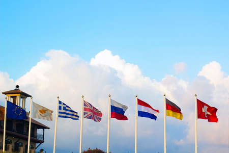 national identity: Flags of different countries flapping in wind against blue sky