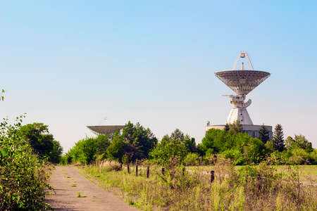 Large satellite dish radar antenna station in field. Space Communication Center