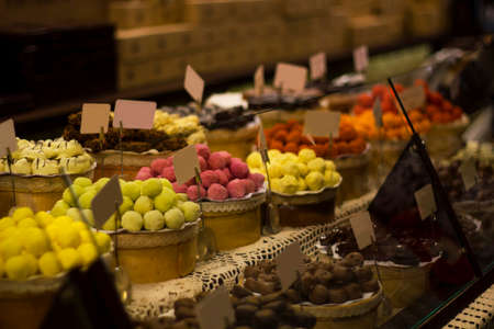 Large selection of chocolates on counter of market store in dark room. Wide assortment of candy selective focus