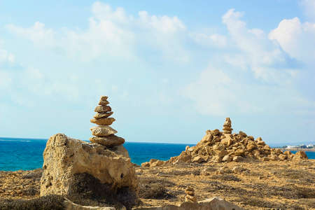 Stones pyramid on background of Mediterranean sea. Seashore background with stone tower. Tower of rocks on beach. Small Zen out of pile of stones on rock. Tombs of Kings, an ancient necropolis in Paphos, Cyprus