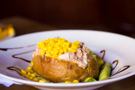 Stuffed potato with tuna and sweetcorn on white plate selective focus