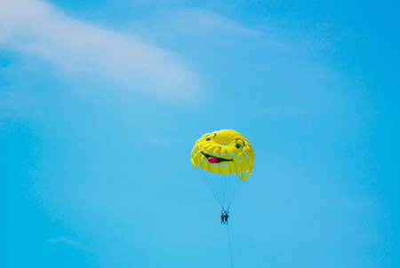 Big yellow fun parachute with painted mug carries people through air against blue sky