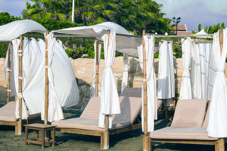 Wooden sunbeds with drapes on sandy beach
