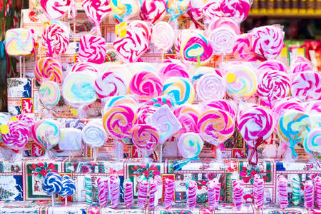 Great choice of colorful lollipops on stick for sale in shop window Stock Photo