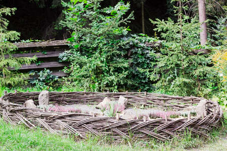 Flowerbed fenced by low wicker fence. Flowers Heather grow in summer garden Banque d'images