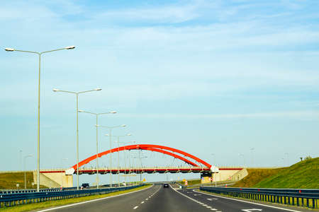 Cars driving on asphalt road. Summer landscape with road, red arch of bridge over track and metal street lamps between green fields against blue sky, sunny day