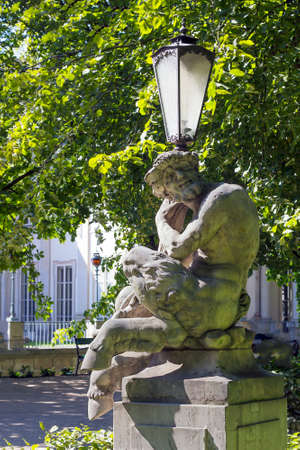 Old street lamp with faun sculpture
