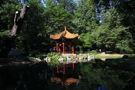 Summerhouse in Chinese style and bridge over pond in park