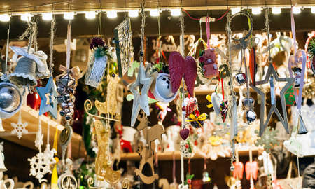 Small wooden handmade toys selling at Xmas Fair. Christmas market with traditional decorations close up. Holidays kiosk with festive gifts and souvenirs at city street Banque d'images