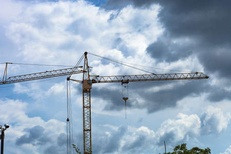 Tower crane by blue sky. Yellow high construction crane building house
