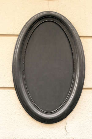 Oval empty blank black signboard on wall. Vintage dark frame board on building, cafe menu