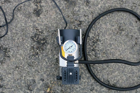 Tire inflator car tool on road. Portable metal air compressor pump for car wheels, driver equipment