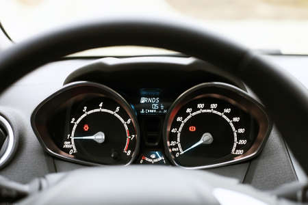 Speedometer, tachometer and fuel level in car. Black automobile instrument panel on dashboard