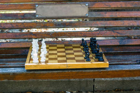 Old chess on wooden bench in public city park. Beginning of game Фото со стока