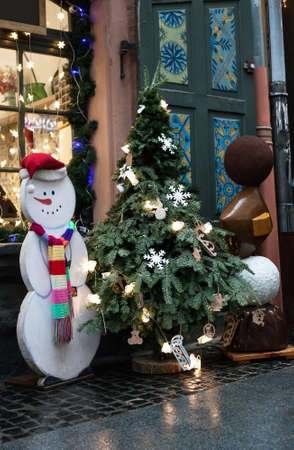 Christmas tree in pot and white Snowman with scarf near house window