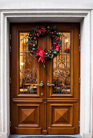 Wooden door with christmas wreath. Decorated woods doorway