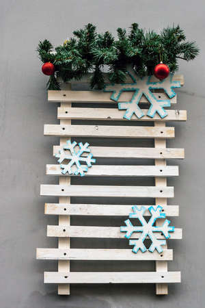 Wooden plank board with fir branches on house wall. Empty Christmas wooden background