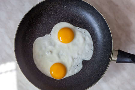 Two fried eggs cooked in frying pan for early breakfast, top view