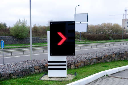 Electronic scoreboard with red arrow pointer on gas station. Digital display on city street Stock fotó