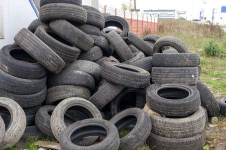 Heap of old used black car tires. Pile of obsolete automobile dump tyres