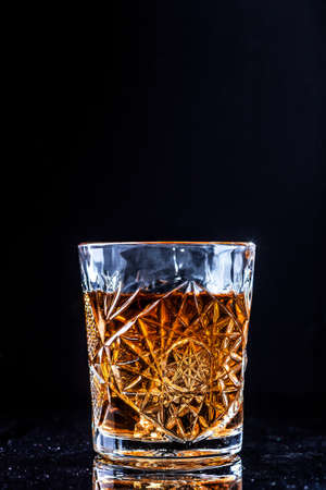 Drinking glass with whiskey on black background. Golden bourbon alcohol drink on table with copy space Фото со стока - 126758662