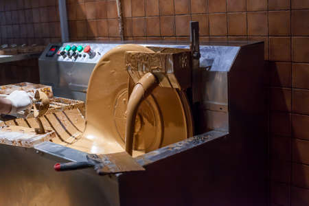 Machine processes and creation of chocolate in dark room. Pouring milk chocolate Фото со стока - 126766866