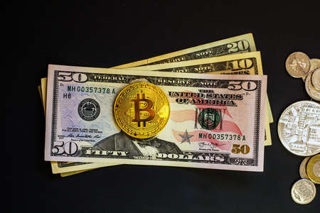 Dollars banknotes and golden bitcoin coin isolated on black background. Traditional and digital crypto currency, top view