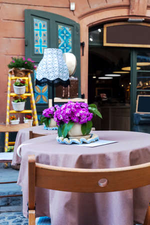 Summer terrace cafe with decorated tables. Table with tablecloth and small vase with decorative bouquet of pink flowers Фото со стока - 126766992