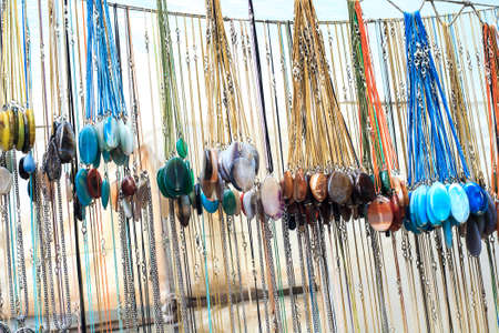 Many gemstone pendants made of colorful natural stones hanging in gift shop. Collection of different necklace sale on street market Reklamní fotografie