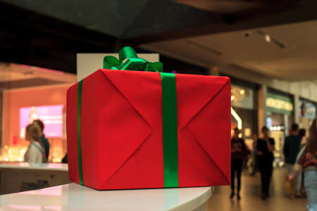 Gift box in red wrapping paper, christmas holidays decor. Birthday present in shopping mall Banco de Imagens - 135532863