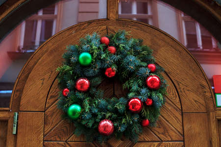 Traditional Christmas wreath from spruce branches hanging on wooden door Stock Photo