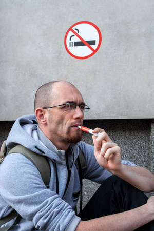 Caucasian man smoke electronic cigarette under sign No smoking at city street. Concept violation of rules at public place. Iqos system in hand