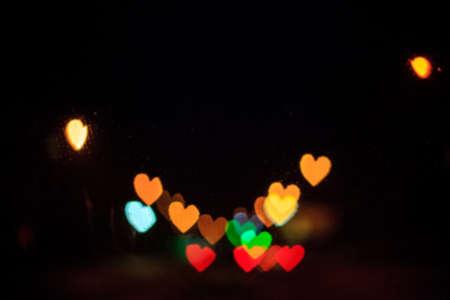 Arrière-plan flou avec bokeh coeur rougeoyant. Défocaliser le papier peint brillant romantique abstrait. Réverbères urbains flous de la Saint-Valentin Banque d'images