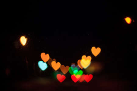 Blur background with glowing heart bokeh. Defocus abstract romantic shiny wallpaper. Valentine day blurry urban street lights
