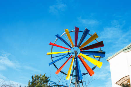 Multicolored small windmill by blue sky. Small wind turbine near house 写真素材