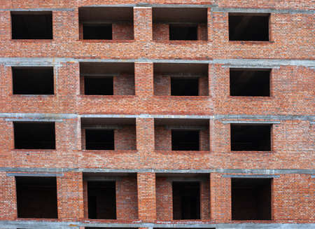 Empty windows in brick multistory house under construction. Part of condominium facade