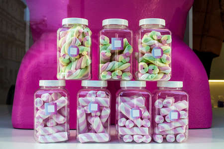 Marshmallows in transparent plastic jars in candy store window for sale 写真素材