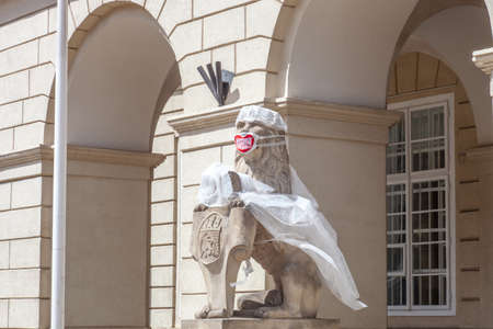 Stone old lion sculpture in white medical coat and mask in city center. Write on mask in Ukrainian