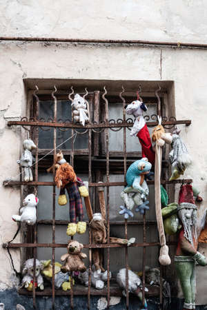 Window with metal bars and hanging old stuffed toys, creepy house