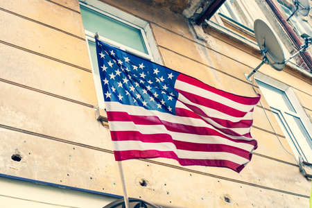 USA flag waving on old house background, vintage style photo 写真素材