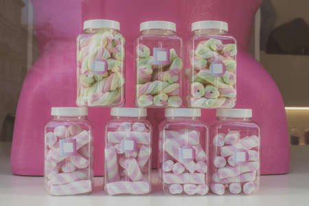 Marshmallows in transparent jars in candy store window, retro colors