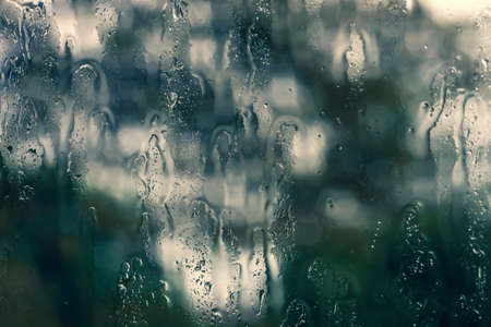 Abstract autumn background with drips of rain outside of window. Rainy summer weather and raindrops on glass close up. Water drops on dark windshield