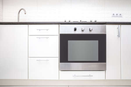 White kitchen cabinet and oven front view. Wooden drawer dishware storage and stove Foto de archivo