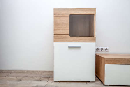 Wooden cabinet in living room. White woods closed sideboard standing by light wall background