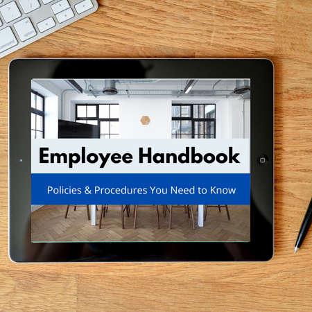 Employee handbook displayed on a tablet sitting on a desktop Stock Photo