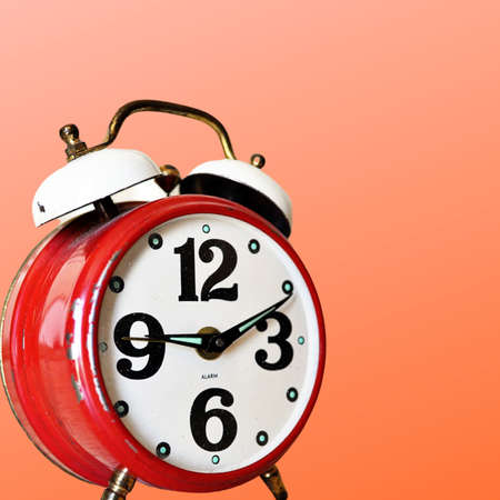 Red alarm clock with large number face and bells on an orange background 版權商用圖片