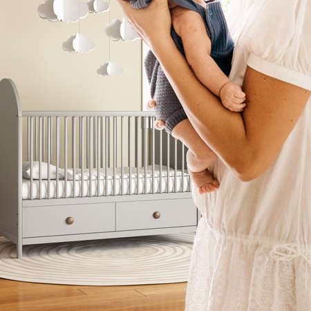 Woman in nursery holding an infant with a grey baby bed in the background Reklamní fotografie